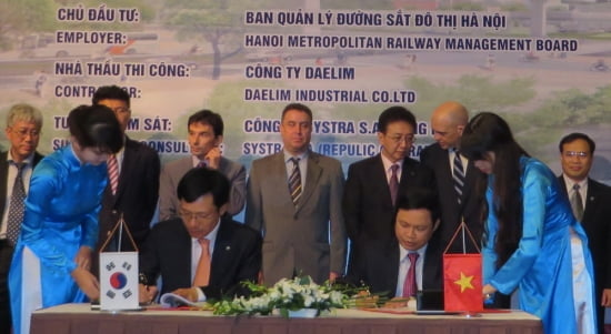 대림산업 김연기 상무(테이블 왼쪽)와 하노이 도시철도 관리위원회 웅이엔 꿩 만 위원장(오른쪽)이 공사 계약서에 서명을 하고 있다.