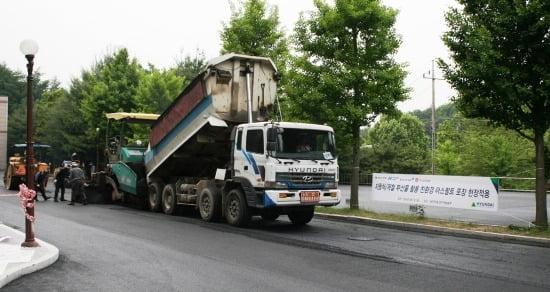 현대건설이 폐차 부품 등을 재활용해 개발한 도로포장공법을 시연하고 있다. <사진제공=현대건설>