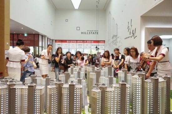감계 힐스테이트 4차의 모델하우스를 찾은 내방객들이 분양 도우미의 설명을 들으며 단지 모형도를 살펴보고 있다.<사진제공=현대건설>