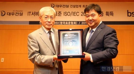 대우건설 이훈복 경영지원실장(오른쪽)과 BSI Korea 천정기 회장(왼쪽)이 ISO/IEC 20000 인증패를 들고 기념촬영을 하고 있다.