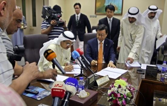쿠웨이트시 소재 쿠웨이트 공공사업부에서 열린 쿠웨이트 도하링크 교량공사 계약식(22일)에서 오두환 GS건설 인프라부문 대표(좌석 오른쪽)와 압둘라지즈 압둘라티프 알이브라힘 쿠웨이트 공공사업부 장관(좌석 왼쪽)이 계약서에 서명을 하고 있다. (GS건설 제공)