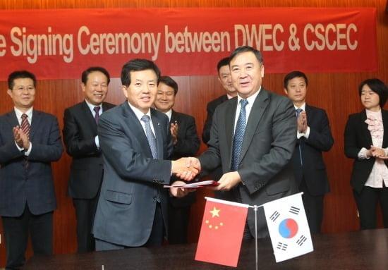 사진설명: 대우건설 박영식 사장(왼쪽)과 중국 CSCEC 황커쓰 8국 회장(오른쪽)이 전략적 제휴 협약서에 서명하고 악수를 나누고 있다. 자료제공 대우건설