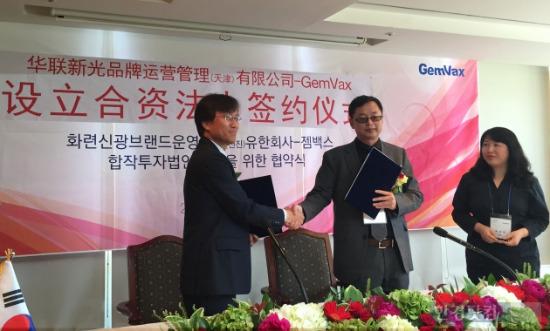 김상재 젬백스 대표(왼쪽)과 쭝쟈웨이 화련신광 대표가 합작사 설립을 위한 계약서에 서명 후 악수를 나누고 있다./