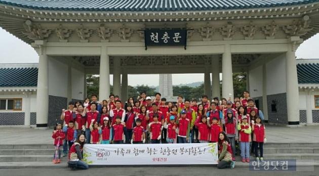 봉사활동에 참여한 롯데건설 임직원 가족들이 현충문 입구에서 단체사진을 찍고 있다. (자료 롯데건설)