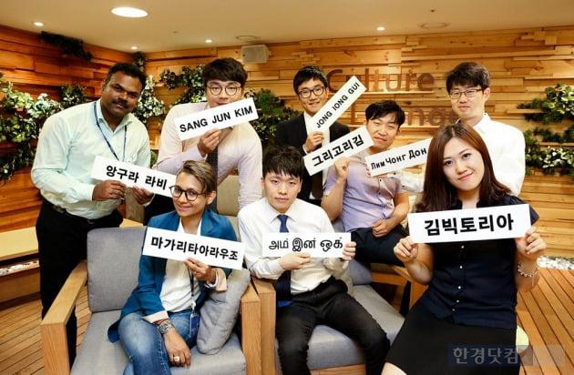 언어 교환 프로그램에 참여하는 외국인 직원들과 한국인 직원들이 오리엔테이션을 마치고 파트너의 모국어로 작성된 이름표를 들고 포즈를 취하고 있다. (자료 현대엔지니어링)
