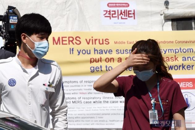 지난 2일 서울 연건동 서울대병원에서 의료진이 마스크를 쓰고 응급실 앞에 설치된 메르스 환자 격리 센터를 지나고 있는 모습. 6일 새벽 국내에서 처음으로 메르스 완치 사례가 나왔다. 한경DB