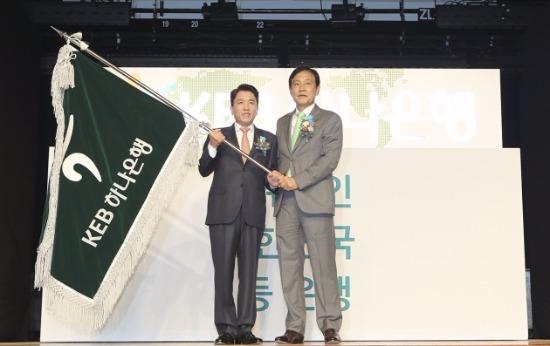 1일 초대 KEB하나은행장인 함영주 은행장(사진 왼쪽)이 김정태 하나금융그룹 회장(사진 오른쪽)으로부터 KEB하나은행 행기를 전달받고 있다.