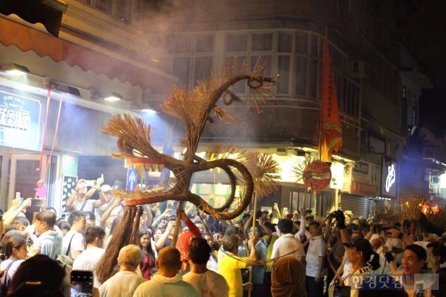 타이 항 파이어 드래곤 페스티벌이 지난 28일 오후 홍콩 코즈웨이 타이 항 운샤스트리트에서 열렸다. 용 머리 모양의 장식물에 불꽃이 피어 오르자 사람들이 춤을 추고 있다. max@hankyung.com