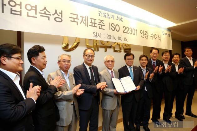 대우건설 지홍근 HSE-Q실장(오른쪽)과 BSI Korea 천정기 회장이 ISO 22301 인증패를 들고 관계자들과 함께 기념촬영을 하고 있다. (자료 대우건설)
