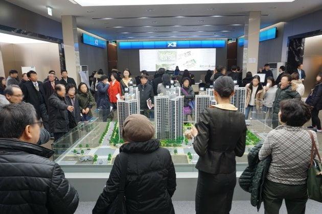 지난 15일 서울 강남구 영동대로 319 자이갤러리 1층에 오픈한 GS건설의 신반포자이 견본주택 내방객들이 단지 모형을 둘러보며 분양 관계자의 설명을 듣고 있다. GS건설 제공