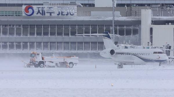 최강 한파로 제주공항에서 항공기 운항이 잠정 중단된 24일 오전 제설차량이 활주로에 쌓인 눈을 치우고 있다. 연합뉴스