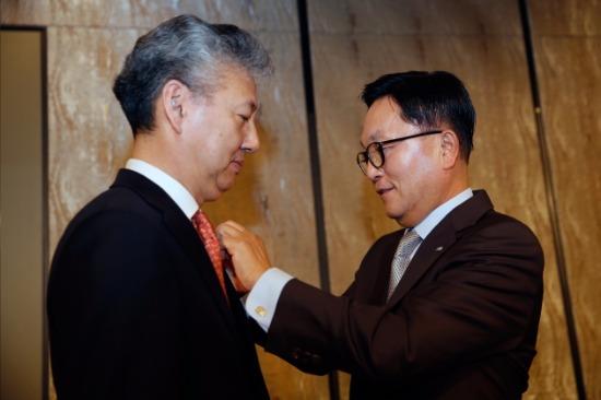 4일 업무보고에 앞서 박현주 회장이 홍성국 사장에게 미래에셋 뱃지를 직접 달아주고 있다.