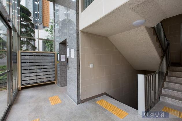 계단 쪽에서 바라본 오렌지로비. 엘리베이터 앞 입주민 대기공간과 1층 가구 전용홀이 완전히 분리된 구조다.