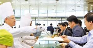 한찬건 포스코건설 대표(왼쪽)가 사내 조직문화 혁신을 위한 '더 플러스' 운동의 일환으로 15일 직원들에게 점심을 배식하고 있다. 포스코건설 제공