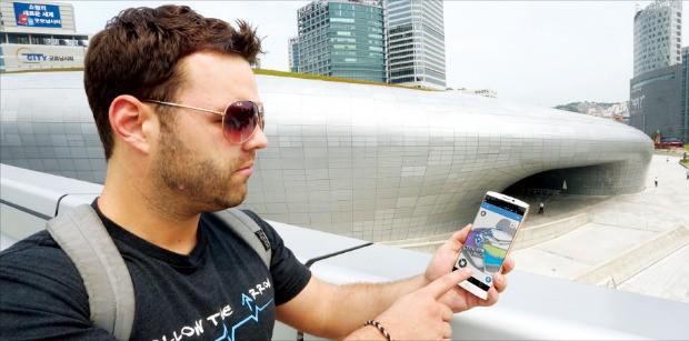 동대문디자인플라자(DDP)를 방문한 외국인이 '스마트 DDP' 앱이 깔린 휴대폰을 통해 전시물 설명을 듣고 있다. LG유플러스 제공