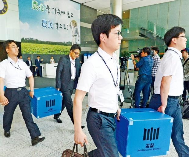 검찰 직원들이 17일 서울 새문안로에 있는 농협중앙회에서 선거 부정 의혹을 받고 있는 김병원 회장의 사무실을 압수수색한 뒤 물품을 들고 나오고 있다. 연합뉴스