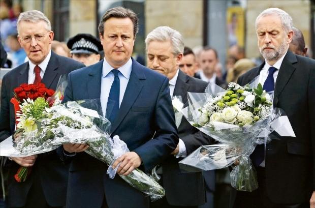 < 헌화하는 캐머런 英 총리 > 데이비드 캐머런 영국 총리(앞줄 왼쪽 )와 제러미 코빈 노동당 대표( 오른쪽)가 17일 조 콕스 노동당 하원의원 피살 현장을 찾아 헌화하고 있다. 이날 캐머런 총리는 영국민에게 포용력을 발휘해줄 것을 촉구하면서 오는 20일 콕스 의원에게 경의를 표하기 위해 의회를 소집할 것이라고 밝혔다. 런던AP연합뉴스
