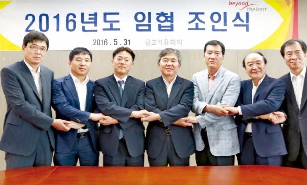 금호석유화학 노사 대표가 지난 5월 서울 을지로 본사에서 무분규로 임금단체협약을 체결한 뒤 손을 맞잡았다.