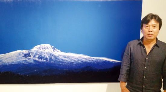 서양화가 김성호 씨가 자신의 작품 '새벽-한라산' 앞에 서 있다.