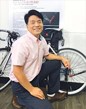 김필호 리만 대표가 받침대와 펌프, 후미등, 타이어 레버 등의 역할을 하는 '킥스탠드 펌프'의 작동 원리를 설명하고 있다. 안재광 기자