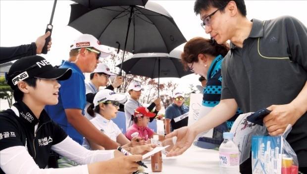 박성현(왼쪽)이 24일 대회 2라운드 경기를 마치고 열린 팬사인회에서 갤러리에게 친필로 사인한 종이를 건네며 웃고 있다. 강은구 기자 egkang@hakyung.com