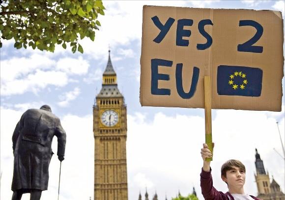 """브렉시트 에 반대하는 한 시민이 지난 23일 """"EU에 '예스'라고 답하자""""는 피켓을 들고 있다. 런던AFP연합뉴스"""