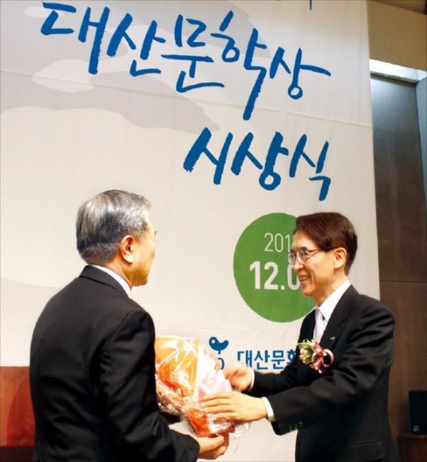 지난해 12월 열린 '제23회 대산문학상 시상식'에서 신창재 대산문화재단 이사장(교보생명보험 회장·오른쪽)이 수상자에게 꽃다발을 건네고 있다. 대산문화재단  제공