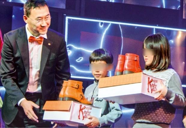 ING생명은 2014년 12월 서울 충무아트홀에서 열린 뮤지컬 '킹키부츠' 공연에 CJ도너스캠프 공부방 어린이 300명을 초청해 함께 관람하는 행사를 열었다. 공연이 끝난 뒤 박익진 ING생명 부사장(왼쪽)이 어린이들에게 '희망 부츠'를 전달하고 있다. ING생명  제공
