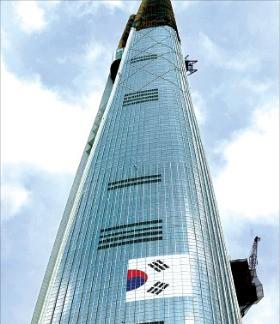서울 잠실 롯데월드타워에 설치된 태극기가 철거되고 있다. 김영우 기자  youngwoo@hankyung.com