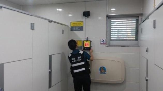 서울 용산구 여성 경찰관이 이태원 공중화장실 내 IoT 비상벨을 점검하고 있다.