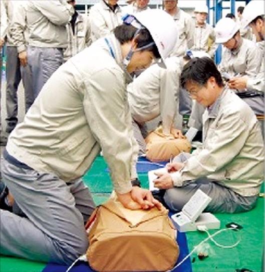 코오롱인더스트리 울산공장 직원들이 지난 6월4일 공장에서 심폐소생술 훈련을 하고 있다.