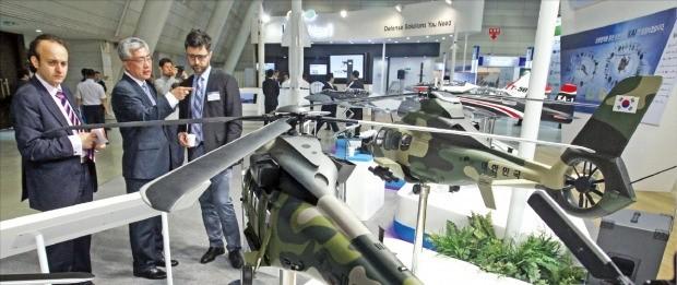 지난달 1일 경남 창원에서 열린 '2016 대한민국 방산부품·장비대전(KDEC)'에서 국내외 방위산업 관계자들이 국산 헬기 모형을 살펴보고 있다. 한경 DB