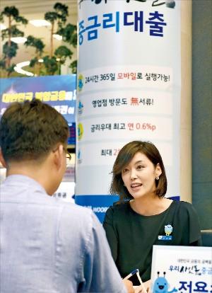 국내 은행이 일제히 중금리 신용대출 상품인 사잇돌 대출을 출시한 5일 서울 중구 우리은행 본점에서 한 고객이 영업점 직원과 가입 상담을 하고 있다. 신경훈 기자 khshin@hankyung.com