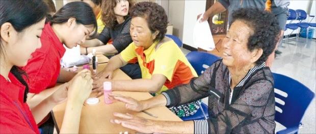 농촌재능나눔캠프에 참가한 대학생들이 네일아트 봉사활동을 하고 있다.
