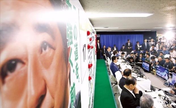 """아베 신조 일본 총리(벽 쪽에 앉은 사람 중 가운데)가 10일 도쿄 자민당사에서 참의원 선거 중간집계 결과에 관해 기자들의 질문을 받고 있다. 그는 """"헌법심사회에서 논의가 수렴된 뒤 국민투표에서 (헌법) 개정을 물을 것""""이라고 말했다. 도쿄AP연합뉴스"""