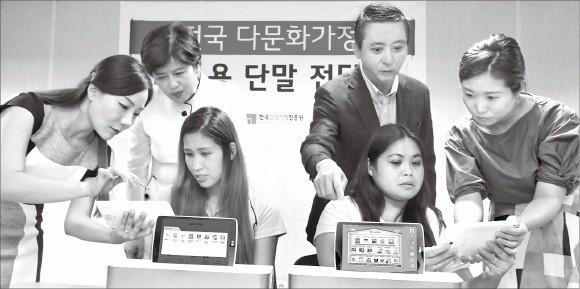 권영수 LG유플러스 부회장(뒷줄 오른쪽)과 강은희 여성가족부 장관(왼쪽)이 지난 11일 서울 동작구 다문화가족지원센터에서 결혼이주여성들과 함께 교육용 단말기를 시연하고 있다. LG유플러스 제공