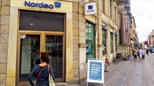 한 고객이 지난 8일 덴마크 코펜하겐 중심가에 있는 노르데아방크로 들어가고 있다. 현금 사용을 점차 줄이고 있는 덴마크에선 현금을 다루지 않는 '노캐시' 점포가 빠르게 늘고 있다. 코펜하겐=김우섭 기자 duter@hankyung.com