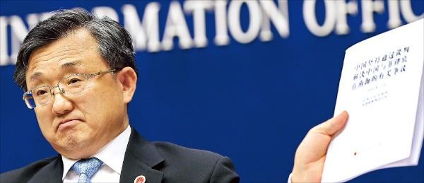 류전민 중국 외교부 차관이 13일 베이징의 국무원 신문판공실에서 내외신 기자회견을 하면서 전날 헤이그 상설중재재판소 판결을 반박하는 내용의 백서를 들어보이고 있다. 헤이그 재판소는 중국의 남중국해 영유권 주장을 인정하지 않는다는 판결을 내렸다. 베이징EPA연합뉴스