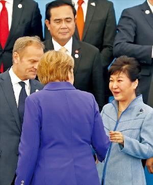 < 메르켈과 반갑게 인사 > 박근혜 대통령이 15일 몽골 울란바토르에서 열린 제11차 아시아유럽정상회의(ASEM)에서 단체 기념사진을 찍기 전 앙겔라 메르켈 독일 총리(뒷모습), 도날트 투스크 유럽연합(EU) 정상회의 상임의장(왼쪽)과 얘기하고 있다. 연합뉴스