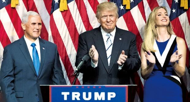 미국 공화당 대선 후보 도널드 트럼프(가운데)가 16일(현지시간) 뉴욕의 한 호텔에서 열린 행사에서 부통령 후보로 공식 지명한 마이크 펜스 인디애나주 주지사(왼쪽), 맞딸인 이방카 트럼프와 나란히 서 박수치고 있다. 뉴욕AFP연합뉴스