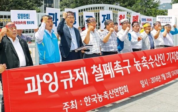 한국농축산연합회 관계자들이 22일 정부서울청사 앞에서 '부정청탁 및 금품 등 수수의 금지에 관한 법률(김영란법)' 적용 대상에서 농·축·수산물 제외를 촉구하는 구호를 외치고 있다. 연합뉴스