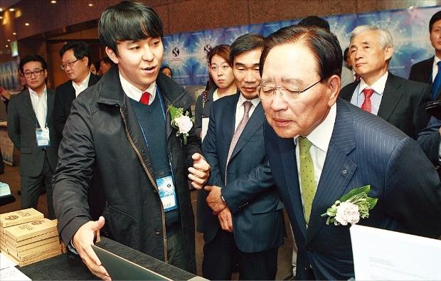 한동우 신한금융그룹 회장(오른쪽)이 서울 여의도 신한금융투자 본사에서 열린 '신한 퓨쳐스랩 데모데이'에서 참여 기업 부스를 돌면서 각 기업의 사업모델에 대한 브리핑을 듣고 있다. 신한금융  제공