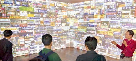 김희수 국립한글박물관 연구관(오른쪽 첫 번째)이 '광고 언어의 힘' 특별전에 전시된 광고 문구에 대해 설명하고 있다. 연합뉴스