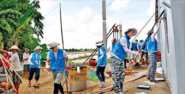 아주그룹 해외자원봉사에 참가한 직원들이 베트남 빈롱지역의 가정집 신축 공사현장에서 일하고 있다. 김정은 기자