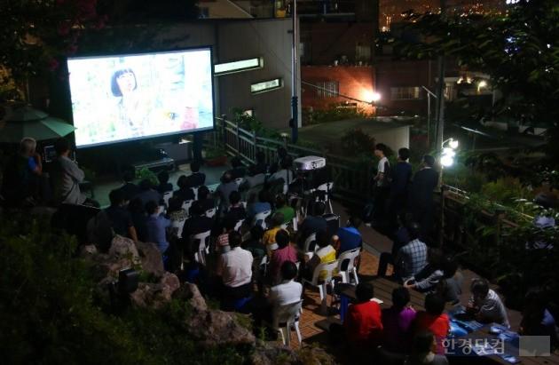르노삼성자동차가 지난달 15일부터 후원하는 '옥상달빛극장'에 지역 주민들이 모여들어 영화를 감상하고 있다. (사진=르노삼성 제공)