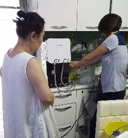 쿠쿠전자의 방문 관리원이 정수기 필터를 교체하고 부품을 청소하고 있다.