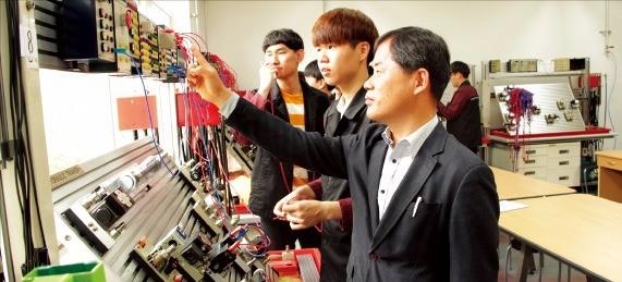 이옥규 한국폴리텍대 진주캠퍼스 자동화시스템과 교수(맨 앞)가 학생들에게 공유압 조절 장치 다루는 법을 가르치고 있다. 한국폴리텍대  제공