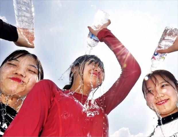 """< """"덥다 더워"""" > 서울의 최고기온이 올 들어 가장 높은 35.7도까지 치솟은 4일 시민들이 서울 여의도 한강공원 수영장에서 얼굴에 찬물을 끼얹으며 더위를 식히고 있다. 김범준 기자 bjk07@hankyung.com"""