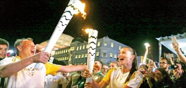브라질의 세계적인 모델 아드리아나 리마(오른쪽)가 4일(현지시간) 리우데자네이루의 마우아 광장에서 안토니우 페드루 리우데자네이루시 관광국장에게 올림픽 성화를 전달하고 있다. AP연합뉴스