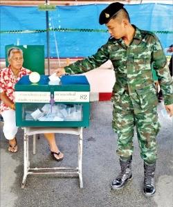 태국 군인이 7일 방콕의 군부대에 마련된 국민투표소에서 헌법개정안 찬반 여부를 결정하는 투표를 하고 있다.   방콕EPA연합뉴스